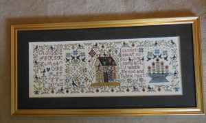 Loose Feathers Mystery Sampler framed.
